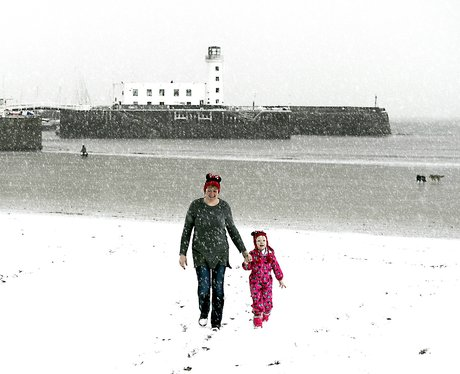 A woman and child enjoy walking on North Bay in Sc